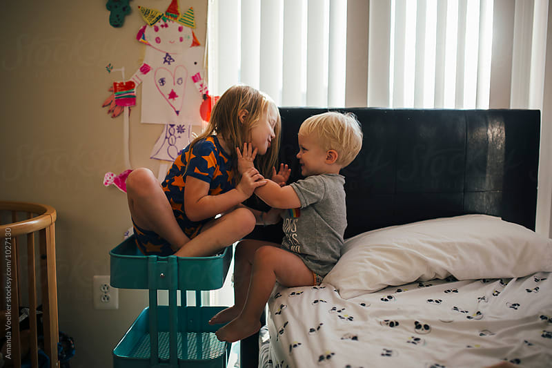 Two young Children Hugging in their room by Amanda Voelker for Stocksy United