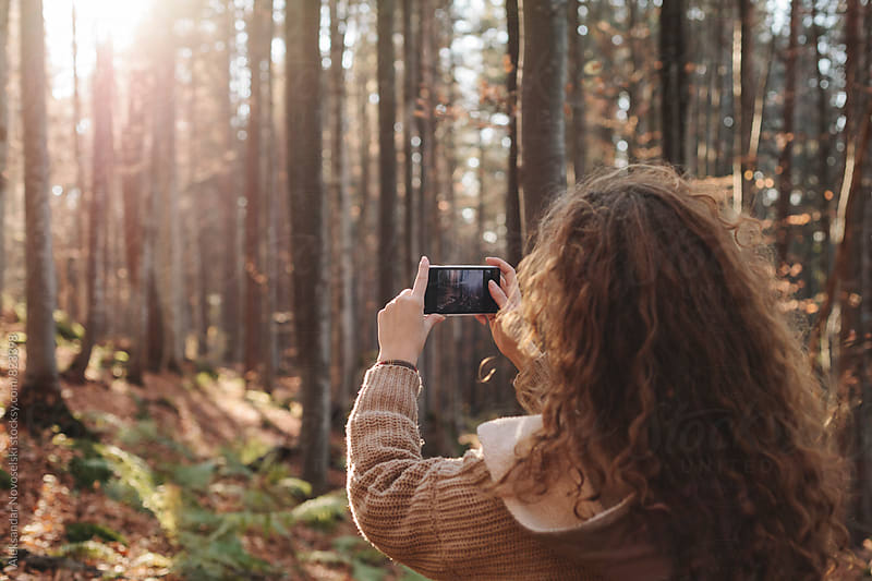 Young woman taking pictures with smartphone in the forest by Aleksandar Novoselski for Stocksy United