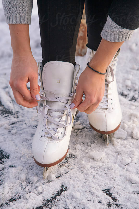 Close-up of woman's hands lacing her skates by Danil Nevsky for Stocksy United