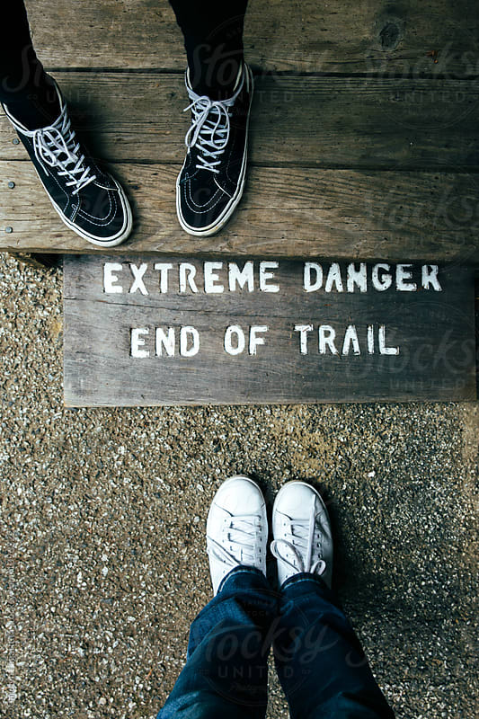 Two feet by a sign that says - Extreme Danger - End of trail by Carolyn Lagattuta for Stocksy United