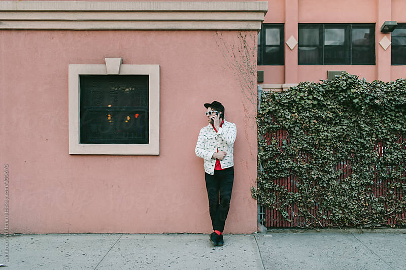 Hipster man making a phone call while leaning on a wall by Cameron Whitman for Stocksy United
