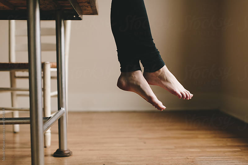 legs and feet hanging off edge of table by Nicole Mason for Stocksy United