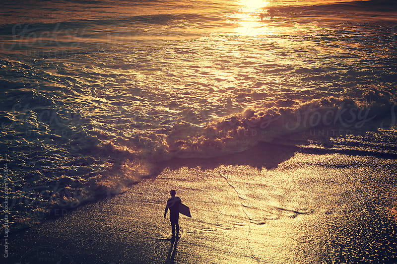 Person in the sand at sunset with a boogie board by Carolyn Lagattuta for Stocksy United