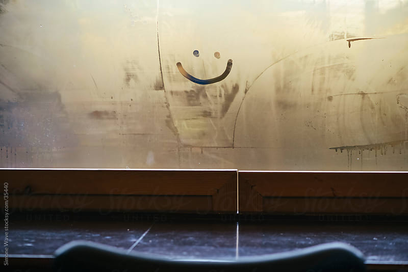 Smiling face on a cafè window by GIC for Stocksy United