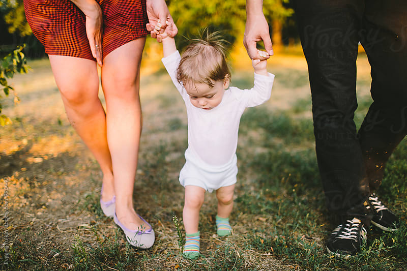 Parents walking with their little baby boy holding hands by Evgenij Yulkin for Stocksy United