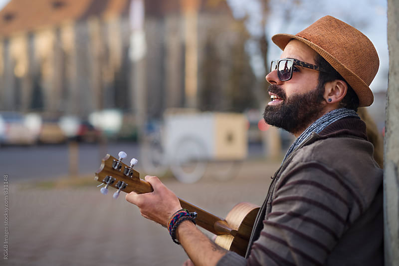 Portrait of young male artist playing music on the street by RG&B Images for Stocksy United