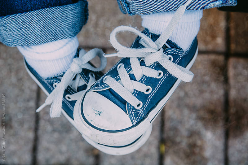 Young child's feet wearing tennis shoes by Gabriel (Gabi) Bucataru for Stocksy United