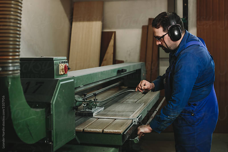 bearded woodworker with black  protection earmuffs working on a belt sander