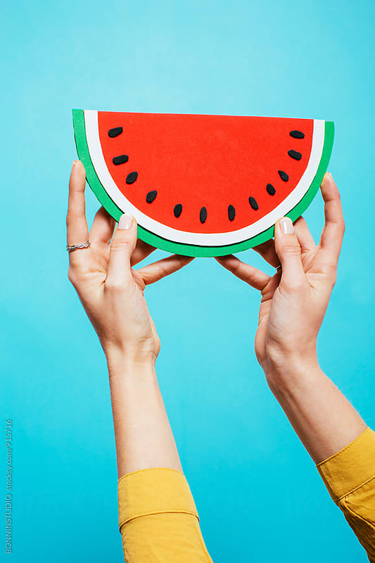 Woman hands holding cardboard watermelon over blue background. by BONNINSTUDIO for Stocksy United
