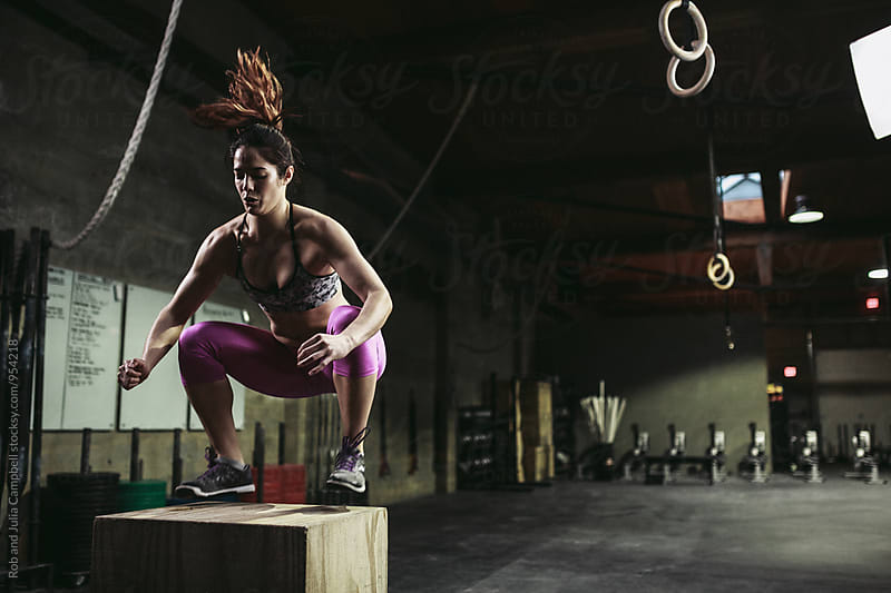Active, fit mixed race woman training hard on box jumps in workout gym by Rob and Julia Campbell for Stocksy United