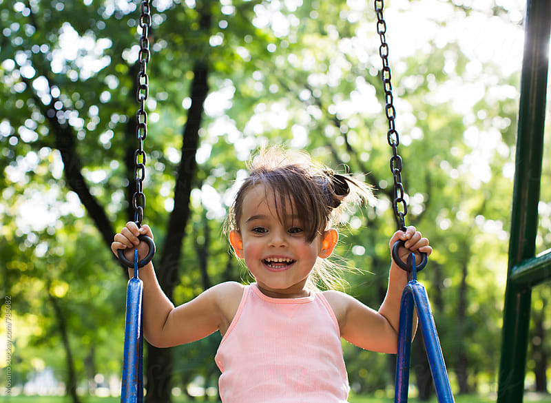 Little Girl on the Swing in the Park by Mosuno for Stocksy United