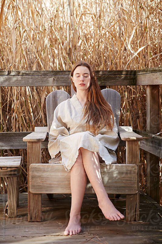 Woman meditating on porch in nature by Trinette Reed for Stocksy United