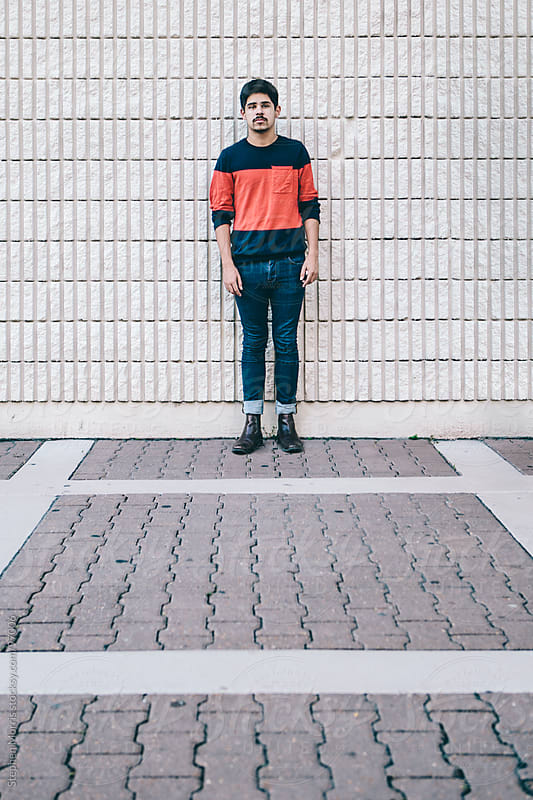 Young Hipster Standing Against Wall by Stephen Morris for Stocksy United