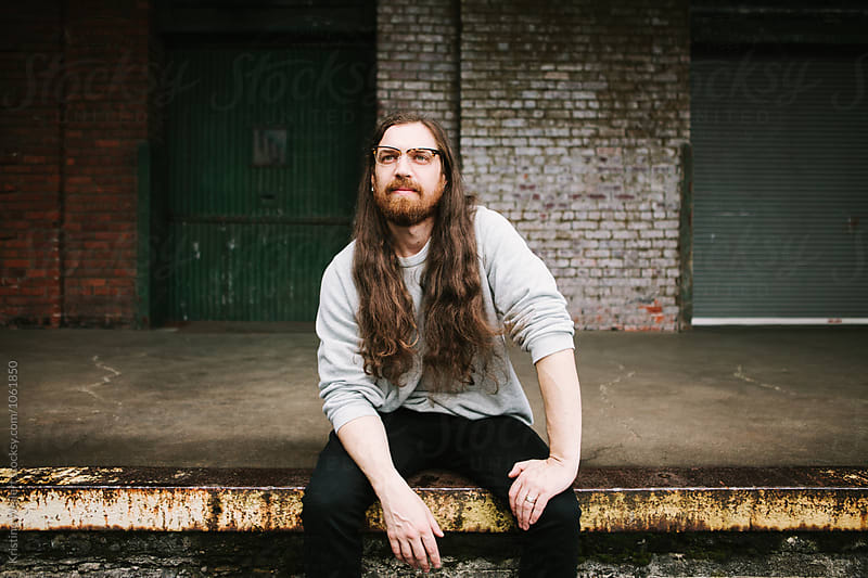 Man sitting on a loading dock with a brick wall behind him by Kristine Weilert for Stocksy United