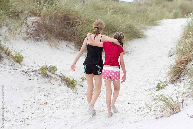 Sisters hug while walking along the beach by Jacqui Miller for Stocksy United