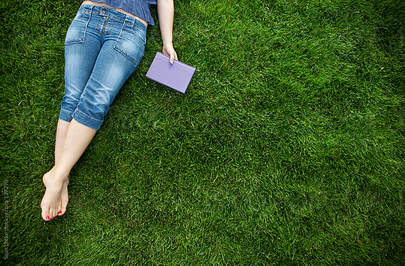 Grass: Woman Takes a Break From Reading by Sean Locke for Stocksy United