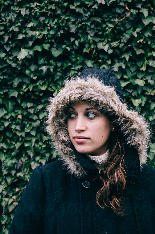 Fashion portrait of young woman wearing a parka coat and a fur hood on ivy green background by Alejandro Moreno de Carlos for Stocksy United