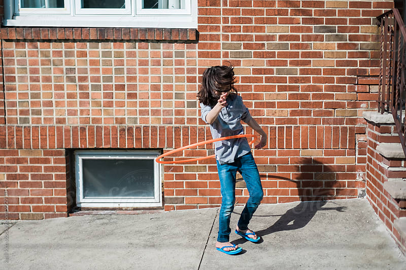 Young boy plays with hula hoop by Kelli Seeger Kim for Stocksy United