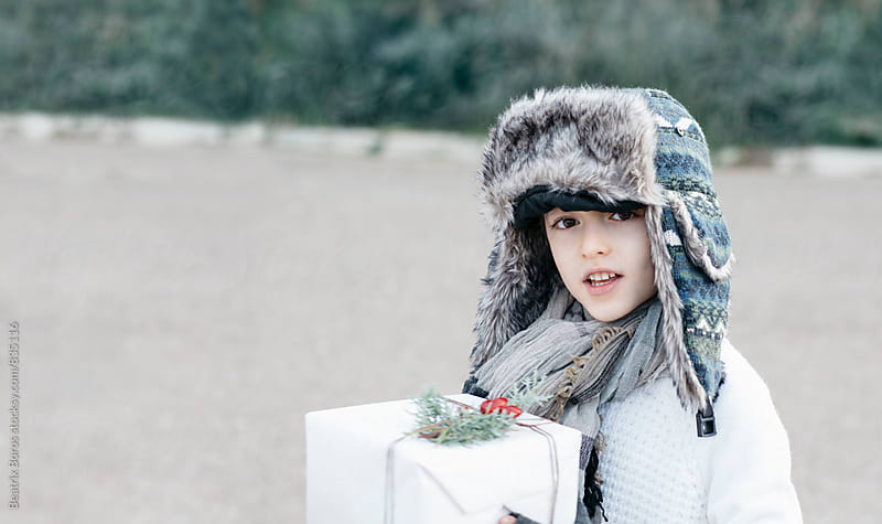 Boy in a warm cap and a festive present box by Beatrix Boros for Stocksy United