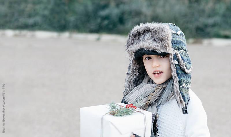 Boy in a warm cap and a festive present box by Beatrix Boros for Stocksy United