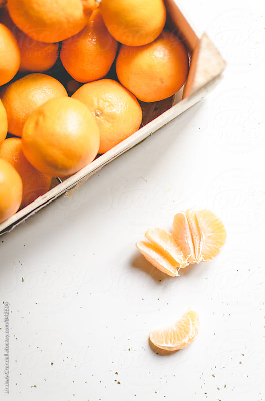 Small oranges in box with peeled orange by Lindsay Crandall for Stocksy United