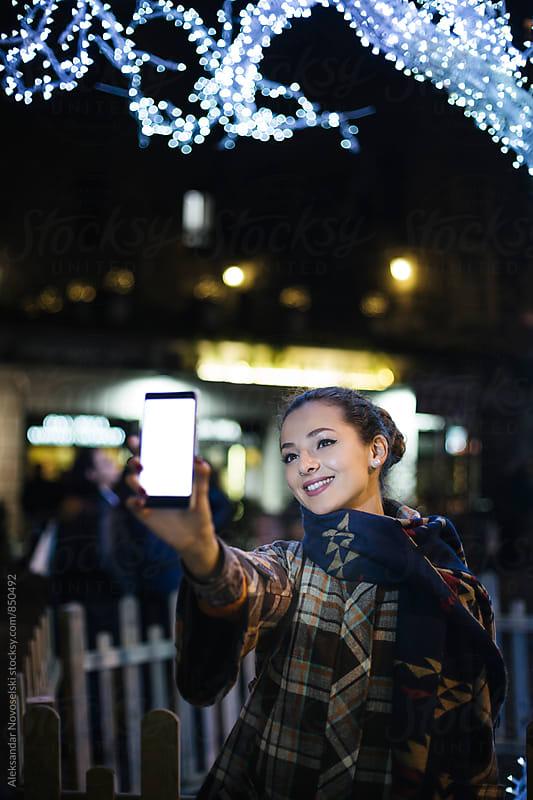 Beautiful woman taking a selfie in urban environment, by night by Aleksandar Novoselski for Stocksy United