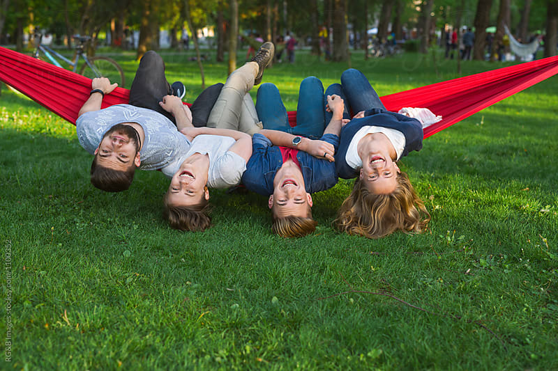 Friends sitting in a hammock upside down by RG&B Images for Stocksy United