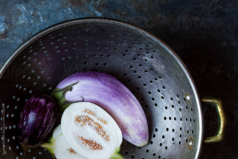 Rinsed eggplants in colander by Nadine Greeff for Stocksy United