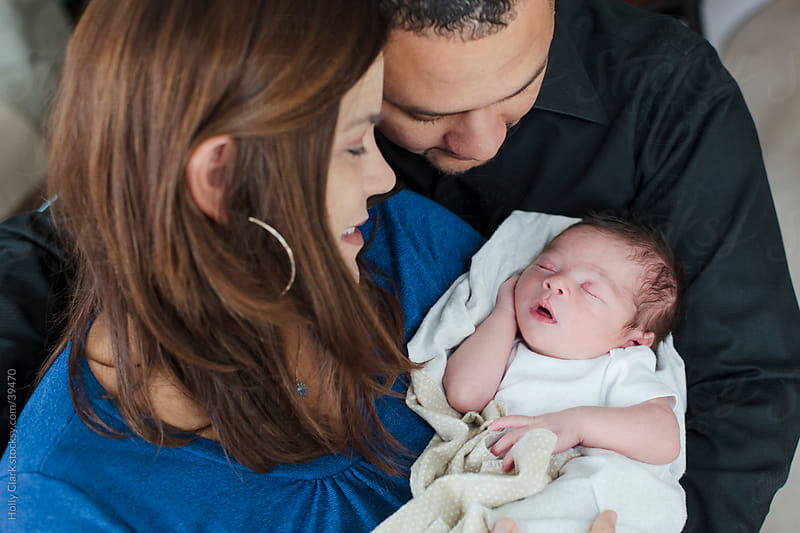 Couple Embrace Their Newborn Son by Holly Clark for Stocksy United