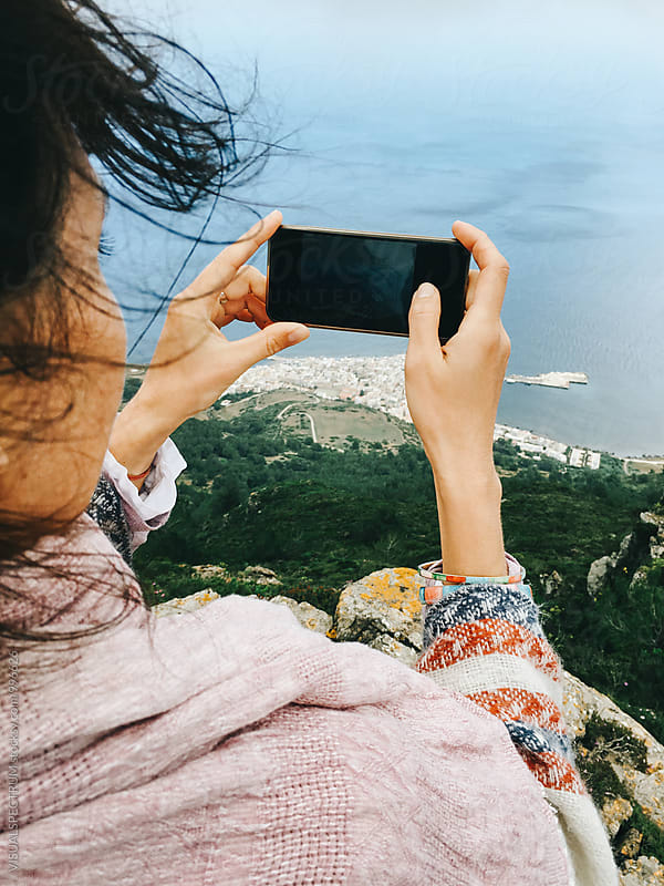 Close Up of Woman Shooting With Smartphone on Windy Island Viewpoint by VISUALSPECTRUM for Stocksy United
