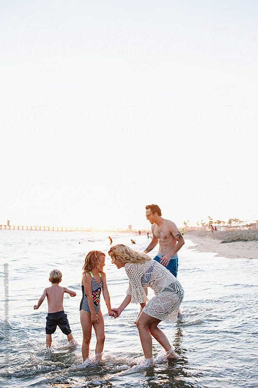 Family on beach at golden hour playing in water by Kristin Rogers Photography for Stocksy United