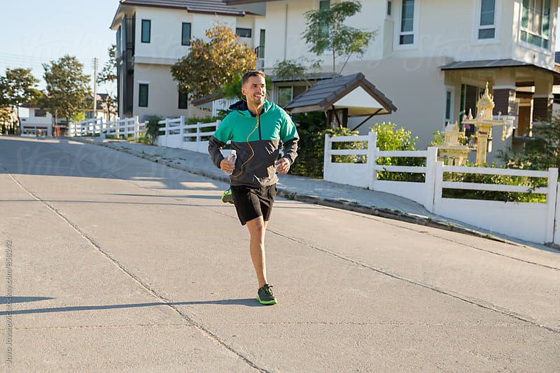 Smiling young athlete running in the street  by Jovo Jovanovic for Stocksy United