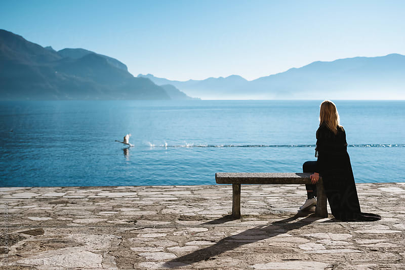 Woman and the swan in Lake Como by Simone Becchetti for Stocksy United