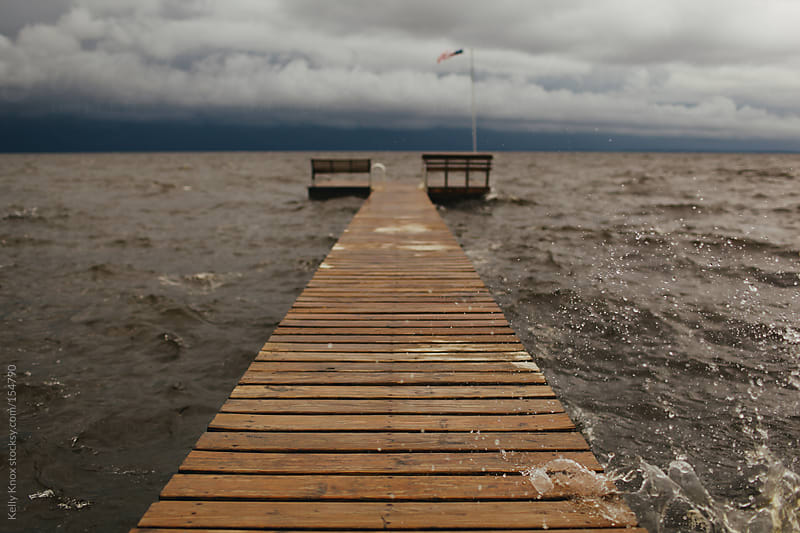 water splashing against a dock during a storm by Kelly Knox for Stocksy United