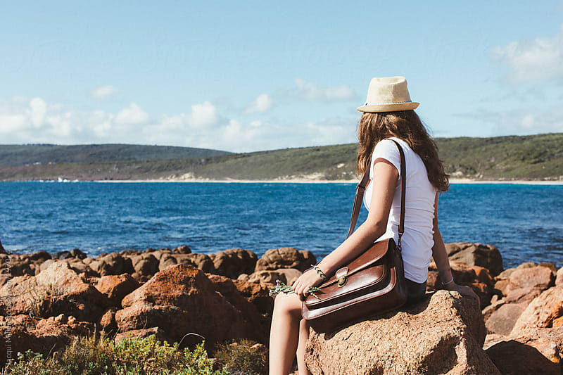 Teen girl with writing satchel sits on a rock and looks at the ocean by Jacqui Miller for Stocksy United