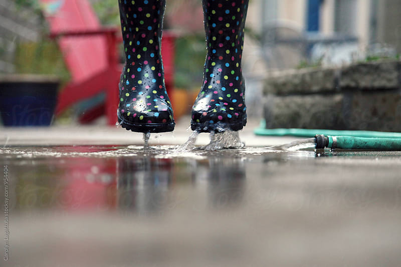 Rain boots jumping with water from the hose by Carolyn Lagattuta for Stocksy United