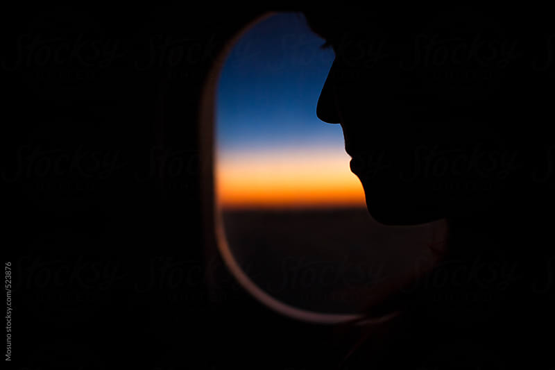 Anonymous Woman Sitting in an Airplane at Sunset by Mosuno for Stocksy United