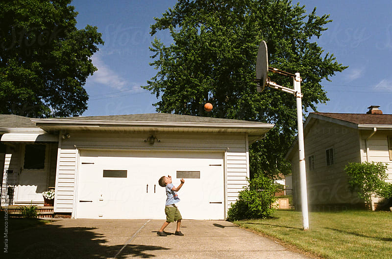 shooting basketball in driveway by Maria Manco for Stocksy United