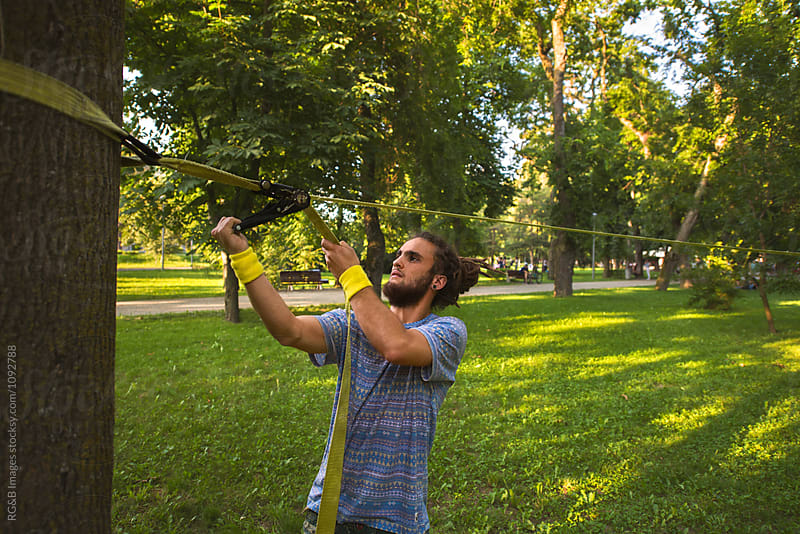 Young bearded man setting up a slackline in the park by RG&B Images for Stocksy United