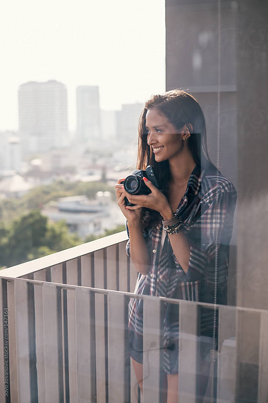 Beautiful girl looking at the city and holding her retro camera. by Jovo Jovanovic for Stocksy United