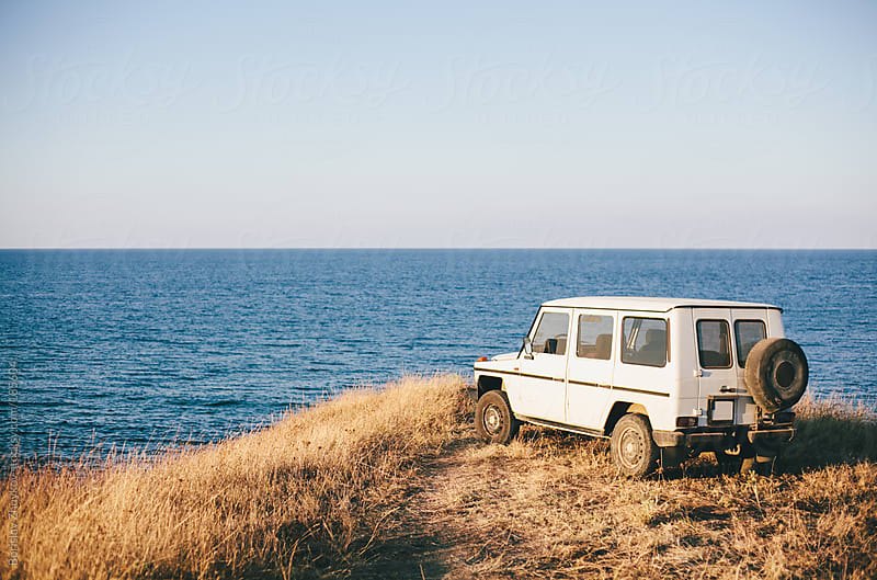 Car on the hill at the sea by Borislav Zhuykov for Stocksy United