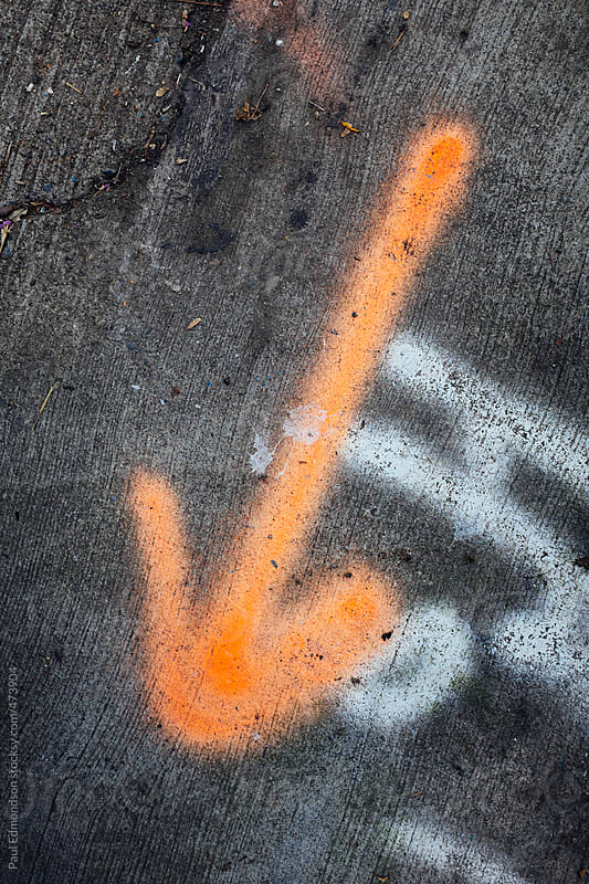 Arrow painted onto urban sidewalk, close up by Paul Edmondson for Stocksy United
