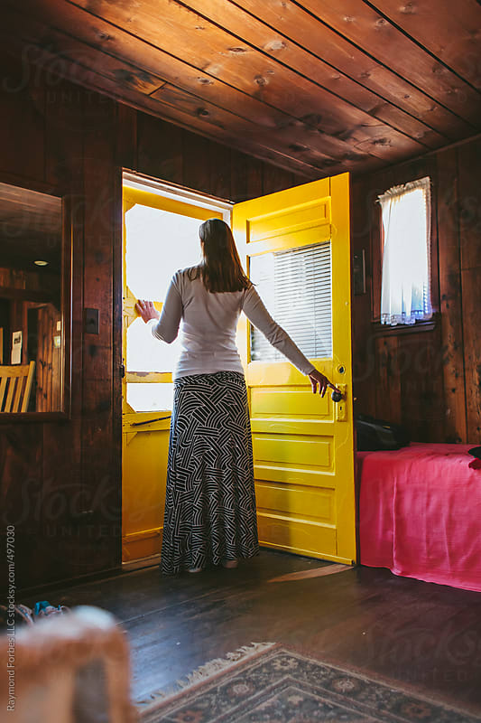 Woman Waiting at Yellow Door in Cabin by Raymond Forbes LLC for Stocksy United