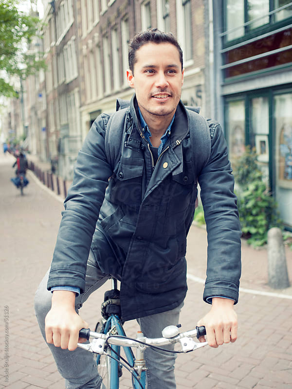 Smiling young man of mixed race standing with his bike on a cobblestone canal street in Amsterdam by Ivo de Bruijn for Stocksy United
