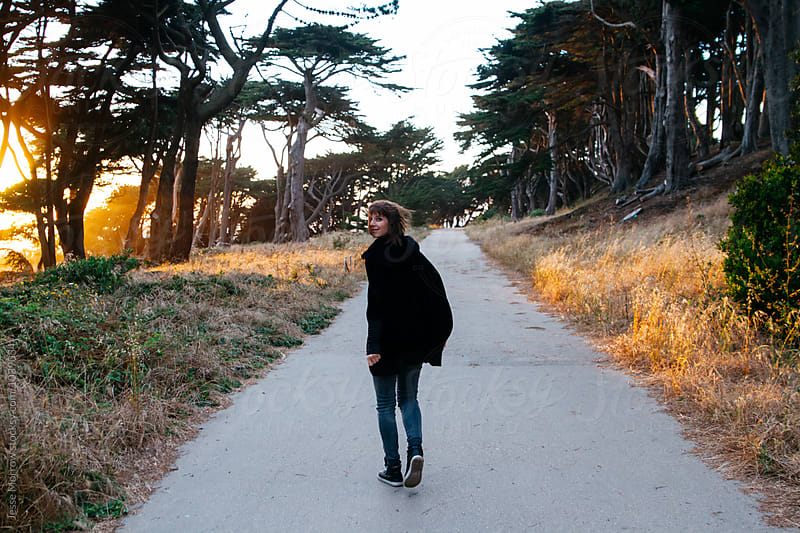 young female woman walks down path on adventure near coast during sunset by Jesse Morrow for Stocksy United