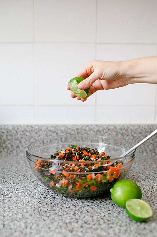 hand squeezing lime into salad by Jennifer Brister for Stocksy United
