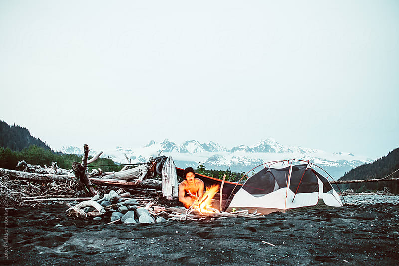 Bare Chested Man Tends To A Campfire At A Makeshift Campsite In The Alaskan Wilderness by Luke Mattson for Stocksy United