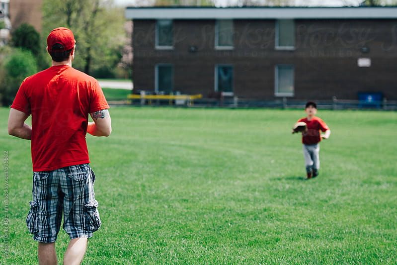 Father and son throwing a baseball before a game by Gabriel (Gabi) Bucataru for Stocksy United
