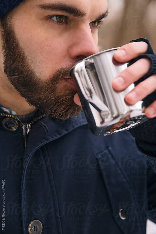 Portrait of young bearded man drinking by Danil Nevsky for Stocksy United