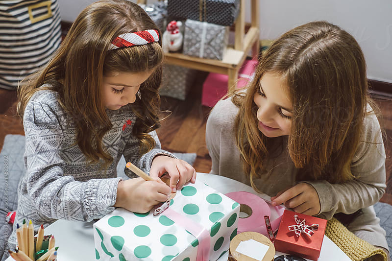 Sisters Wrapping Presents  for Christmas by Aleksandra Jankovic for Stocksy United